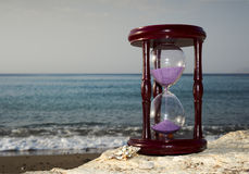 Hourglass on sandy marine beach Royalty Free Stock Photos
