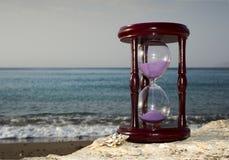 Hourglass on sandy marine beach Royalty Free Stock Photos