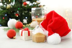 Hourglass with Santa hat and decor on table. Christmas countdown Stock Image