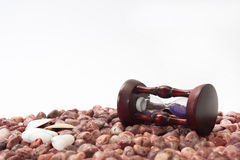 Hourglass and sea shells on the beach with red stones Royalty Free Stock Photos
