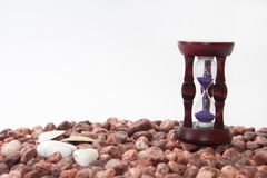 Hourglass and sea shells on the beach with red stones Stock Photography