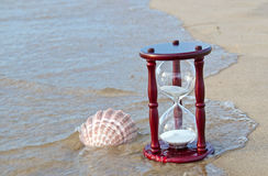 Hourglass with seashell on seashore Stock Photography