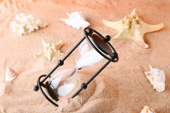 Hourglass with seashells. Black hourglass with seashells on the beach sand Stock Images