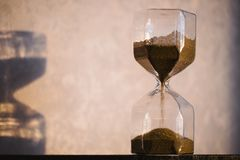 Hourglass with shadow on wall. Time passing concept for business deadline, urgency and running out of time. Sandglass. Egg timer showing the last minute or Stock Images