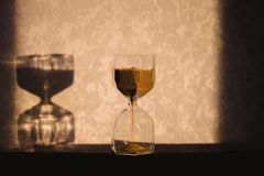 Hourglass with shadow on wall. Time passing concept for business deadline, urgency and running out of time. Sandglass. Egg timer showing the last minute or Royalty Free Stock Image
