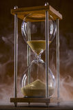 Hourglass and smoke. Hourglass on a wooden table and Mystic Smoke Royalty Free Stock Photography
