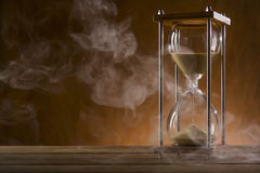 Hourglass and smoke on a wooden table Royalty Free Stock Images
