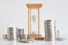 Hourglass and some coin heaps against a white background. Royalty Free Stock Photos