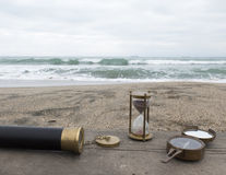 Hourglass, spyglass and compass on the background of the sea in Royalty Free Stock Photos
