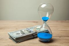 Hourglass and stack of money dollars of banknotes royalty free stock photography