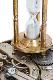 Hourglass standing on the open clockwork of a pocket watch Royalty Free Stock Photo