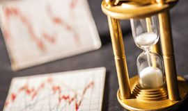 Hourglass and stock quotes concept investment. Sand trickles through an hourglass with graphics showing stock prices in the background. Symbol for the time royalty free stock image