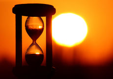 Hourglass in sunset. Hourglass in sky sunset showing the finish time stock image