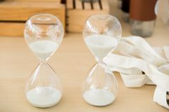 Hourglass on table. Clear hourglass with white sand inside on wooden table Royalty Free Stock Photo