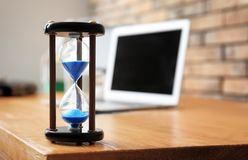 Hourglass on table in office. Time management concept royalty free stock photos