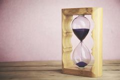 Hourglass on table. Retro hourglass on the wooden table Royalty Free Stock Image