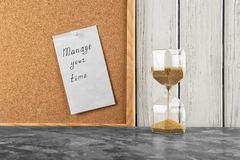 Hourglass on table and sheet of paper with phrase \'Manage your time\' on board stock photos