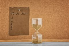 Hourglass on table and sheet of paper with to-do list on board. Time management concept royalty free stock images