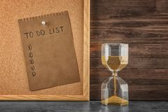 Hourglass on table and sheet of paper with to-do list on board. Time management concept stock images