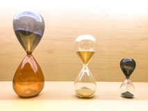 Hourglass. Three different sizes of hourglass with wooden background royalty free stock images