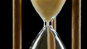 Hourglass is ticking. Yellow sand. Black. Close up. Yellow sand flowing through an hourglass, sand in an hourglass is slowly slipping through a hole, yellow sand stock footage