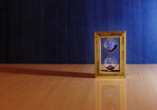 Hourglass, time. On the background of an hourglass, side light, falls the shadow and the reflection stock images