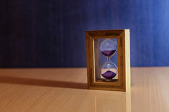Hourglass, time. On the background of an hourglass, side light, falls the shadow and the reflection royalty free stock photos