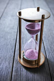 Hourglass Time Object. An hourglass on a grey wood background Stock Images