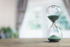 Hourglass time passing in room by window stock photo