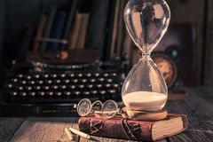 Hourglass and typewriter as memories of old journeys. On old table royalty free stock photos