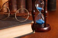 Hourglass und alte Bücher Stockbild