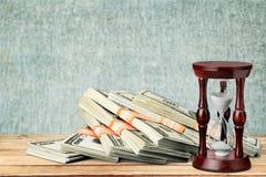 Hourglass und Geld stockbild