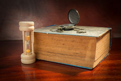 Hourglass and watch with antique book. Royalty Free Stock Photos