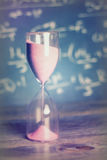 Hourglass on wood with a blackboard background Stock Image