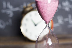 Hourglass on wood with a blackboard background Royalty Free Stock Photos