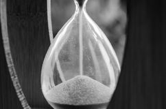 Hourglass in a wood box with blue sand. In black and white on a macro close-up Royalty Free Stock Images