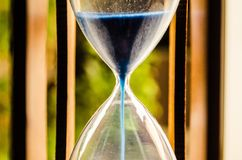 Hourglass in a wood box with blue sand. In a macro close-up. Showing the passing time Royalty Free Stock Photo