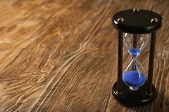 Hourglass on wooden background. Time management concept royalty free stock photo
