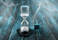 Hourglass on a wooden background. Time is money concept.  stock photos
