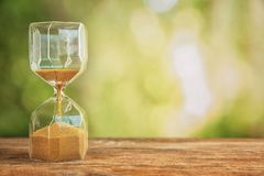 Hourglass on wooden table outdoors. Time management concept royalty free stock images