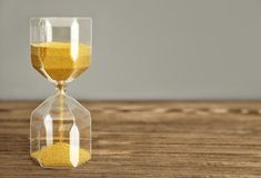 Hourglass on wooden table. Time management concept stock photography