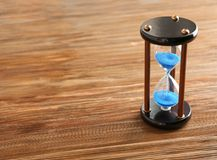 Hourglass on wooden table. Time management concept stock image