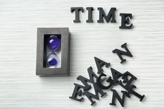 Hourglass and word Time composed from letters on table. Time management concept stock photography