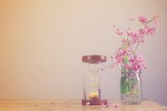 Hourglass z kwiatami na drewnianym tle Obrazy Royalty Free