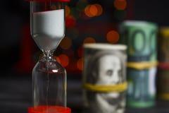 Hourglass z wiązką dolary i euro obraz stock