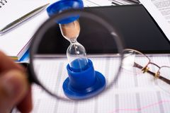 hourglass Zakenman die in het bureau op de achtergrond werken De tijd van het concept is geld Royalty-vrije Stock Afbeeldingen