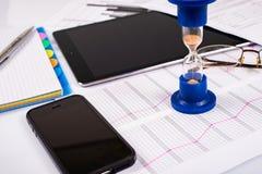 hourglass Zakenman die in het bureau op de achtergrond werken De tijd van het concept is geld Stock Afbeelding