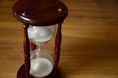 Hourglass, zegar przed drewnianym tłem z tekst przestrzenią Czas biega daleko Zdjęcie Royalty Free