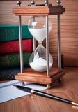 Hourglasses. And book on a wooden table Stock Photo
