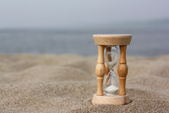 Hourglasses against sandy beach and sky. Ina day Royalty Free Stock Photography